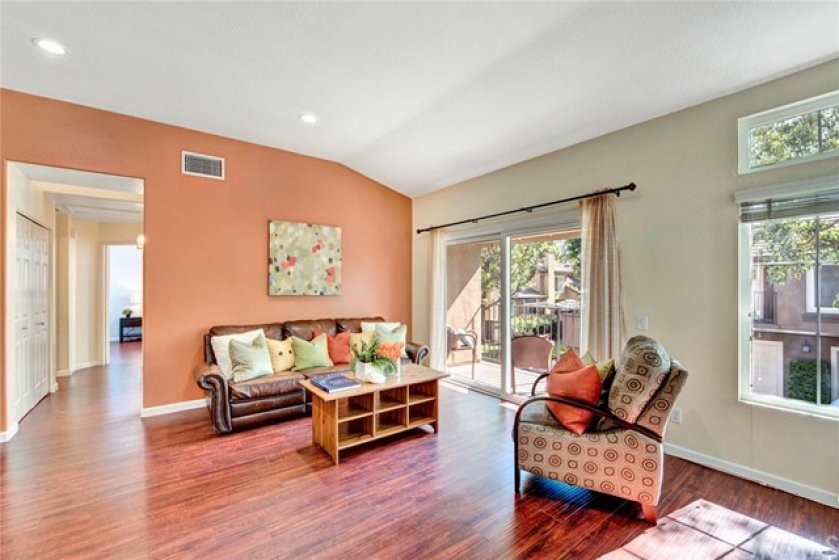 Enter into the home and this comfortable living room with cathedral ceilings, attached deck and beautiful wood flooring that flows through the home.