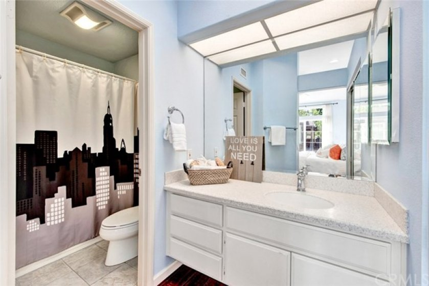 The master bath also has a large vanity with Corian counter top and a privacy door separating the vanity from the commode and tub/shower combo.