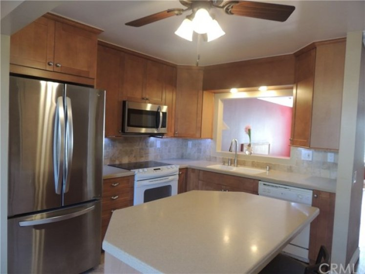 Remodeled kitchen with newer cabinets, under cabinet lighting, quartz counter tops, tile back splash and center island with extra storage