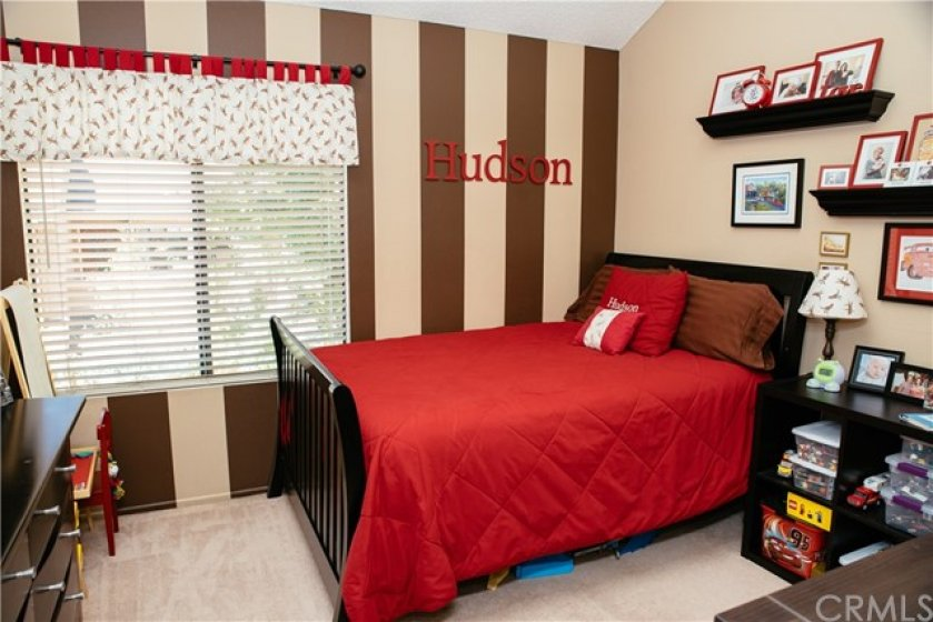Delightful secondary bedroom with vaulted ceilings, striped designed paint, and walk in closet!