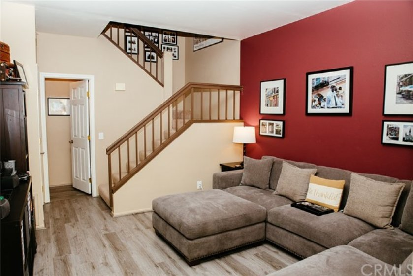Open staircase with newer vinyl plank floors and custom paint colors greet you as you walk through the front door.