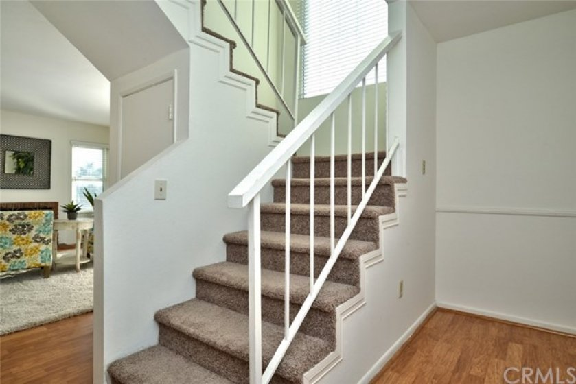 A view from the foyer looking at the staircase with designer accent molding. To the left you see the living room and the entry door is to the right.