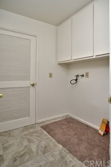 The laundry room with storage cabinets sits between the kitchen and the 2 car attached garage.