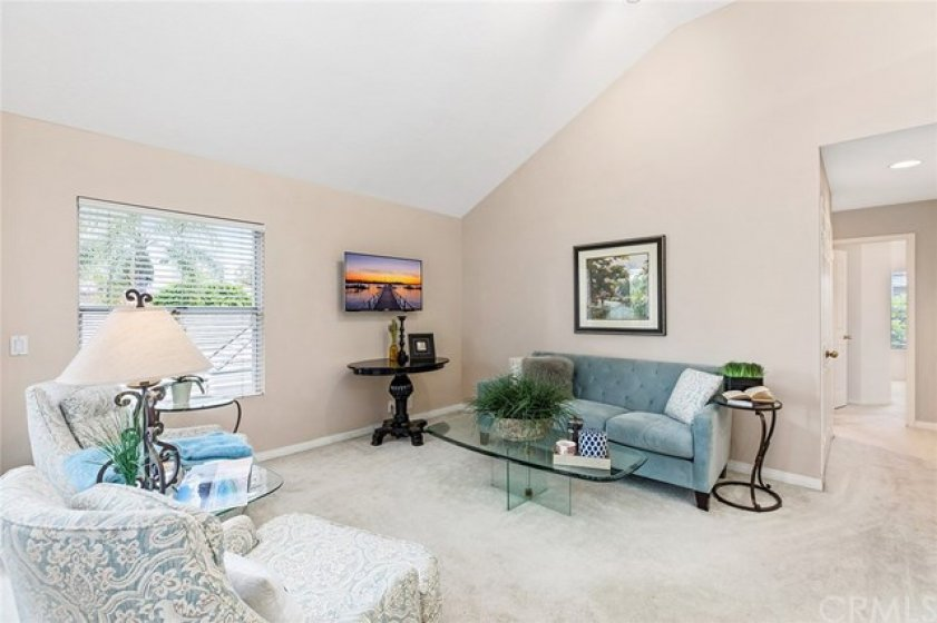 Open living room with vaulted ceilings, open to the kitchen and dining room.