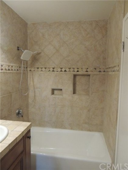 Upstairs full bath has been remodeled with newer tub, tiled shower, vanity, lighting and fixtures