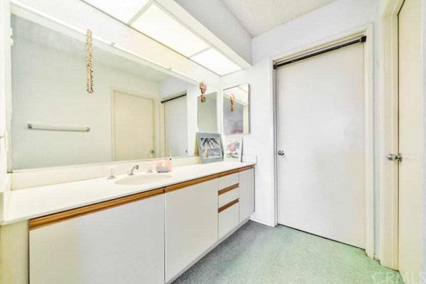 Sink and cabinets in the master with the full bath to the right and walk-in closet straight ahead.