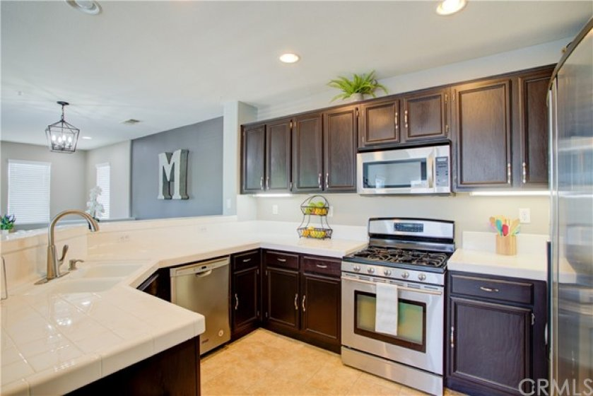 Sparkling clean, open concept kitchen with stainless steel appliances.