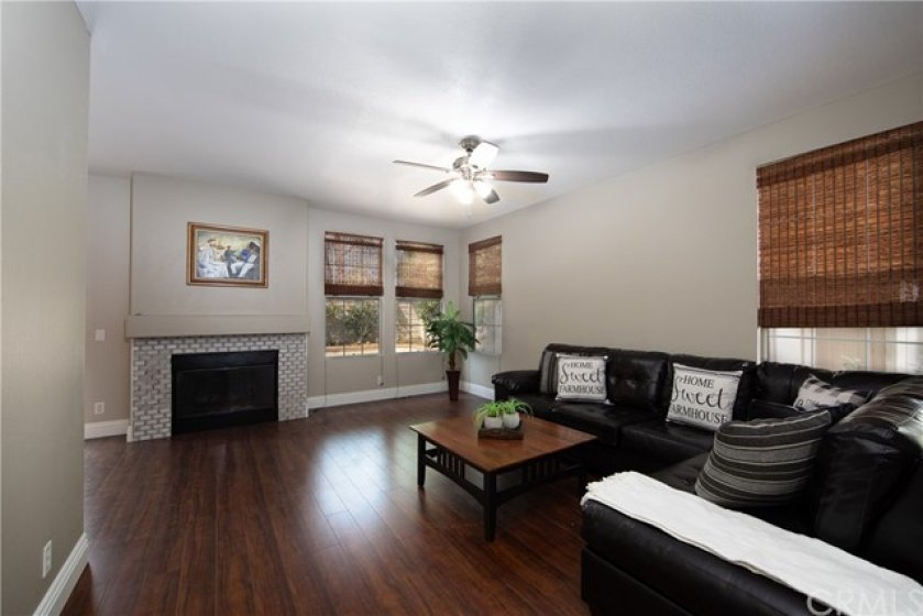 Lovely Living Room complete with gas log fireplace with gorgeous custom stone mosaic surround.