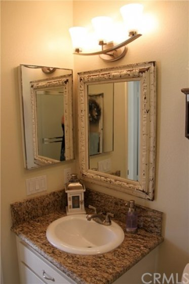 Upgraded granite countertop and beautiful framed mirror
