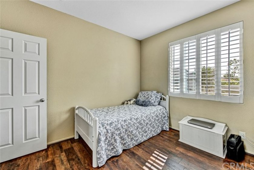 Spacious guest bedroom with wood laminate flooring and plantation shutters