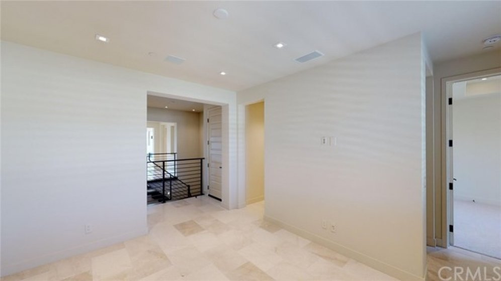 """Den/loft off of the secondary bedroom """"wing"""" of the home.  Door next to the stairs is level two of the elevator."""