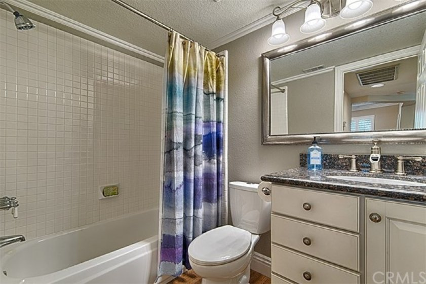 Downstairs full bath with white cabinetry & granite counter top.