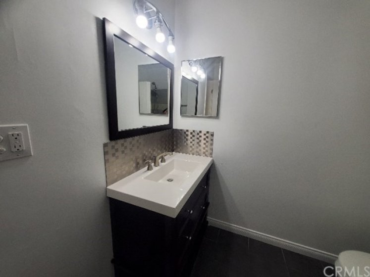 Updated bathroom with contemporary backsplash and new light fixture.