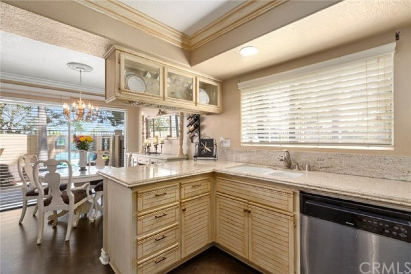 Antique finished cabinets with rope trim- Antique finish extended to crown molding- Kitchen window looks out to greenbelt
