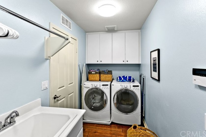 Large laundry room downstairs with cabinets and utility sink.