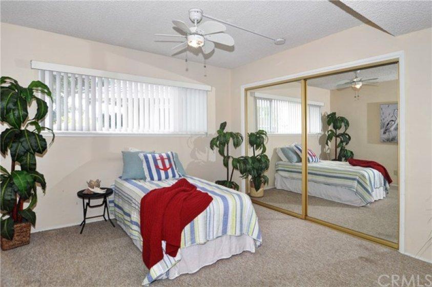 Guest bedroom with mirrored closet doors