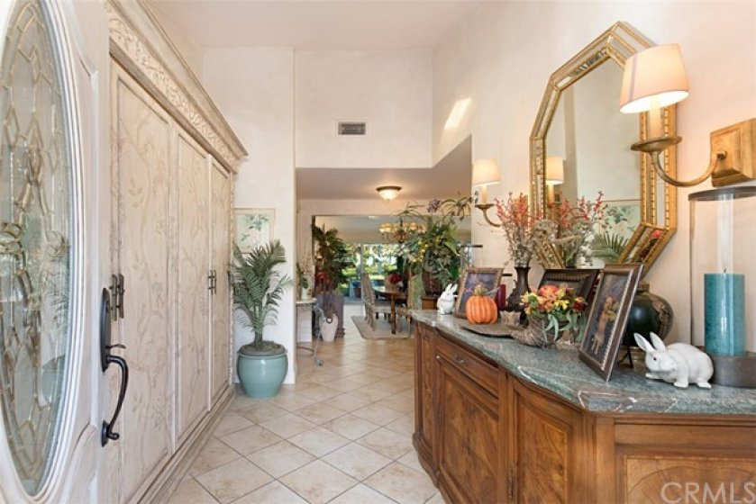 Large foyer with vaulted ceilings and view straight to the back greenbelt.