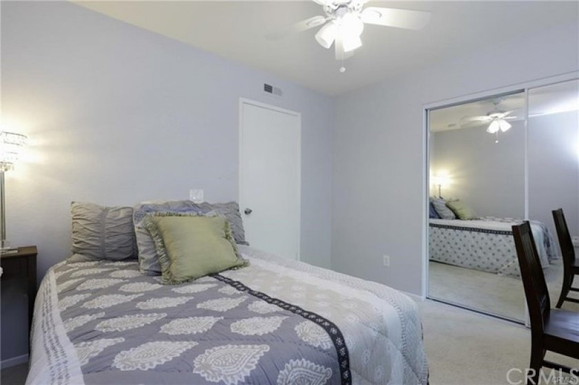 Secondary carpeted bedroom with dual-mirrored closet.