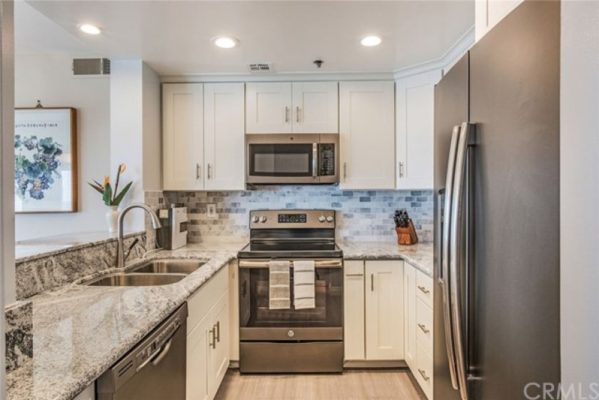 Stunning newly remodeled kitchen with granite counter tops,marble subway tiled backsplash, New GE Modern Slate Grey matte finish,New Custom Cabinetry with European Hinges and Pulls,Dual stainless steel sink,recessed lighting,and more!