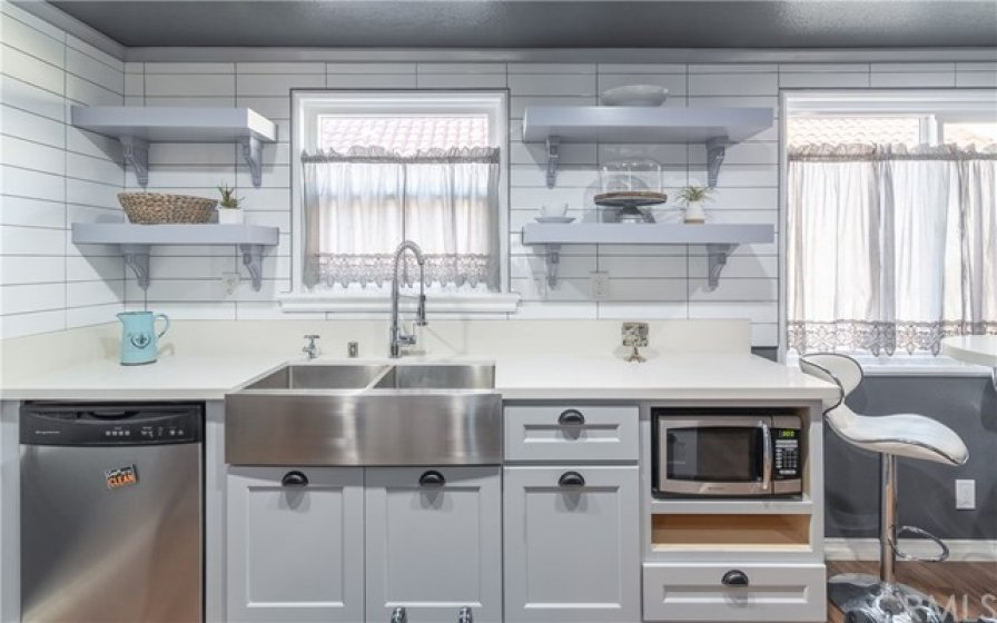Newer Kitchen with quartz counter tops, open shelving and newer stainless steel sink and faucet.