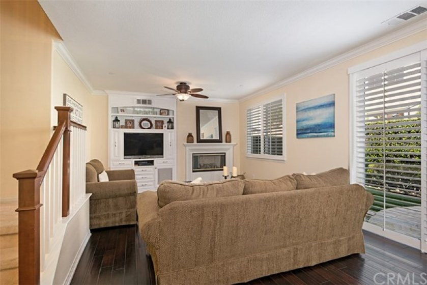 The living room has entertainment cabinetry, cozy fireplace and plantation shutters