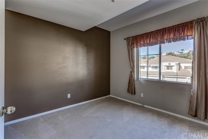 The upstairs guest bedroom features brand new carpet, vaulted ceilings and a sliding mirrored closet.