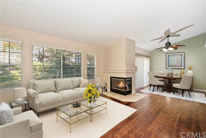 Open floorplan with vaulted ceilings, dual sided fireplace and beautiful wood flooring.Virtually staged.