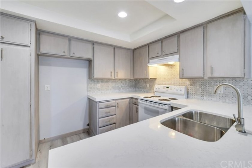 Kitchen with new countertop, backsplash, recessed lights, sink and faucet.