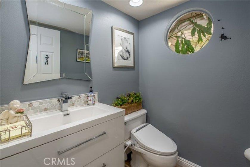 Bathroom #3 is a powder room downstairs. New sink/vanity, backsplash, mirror, paint, toilet, lights.