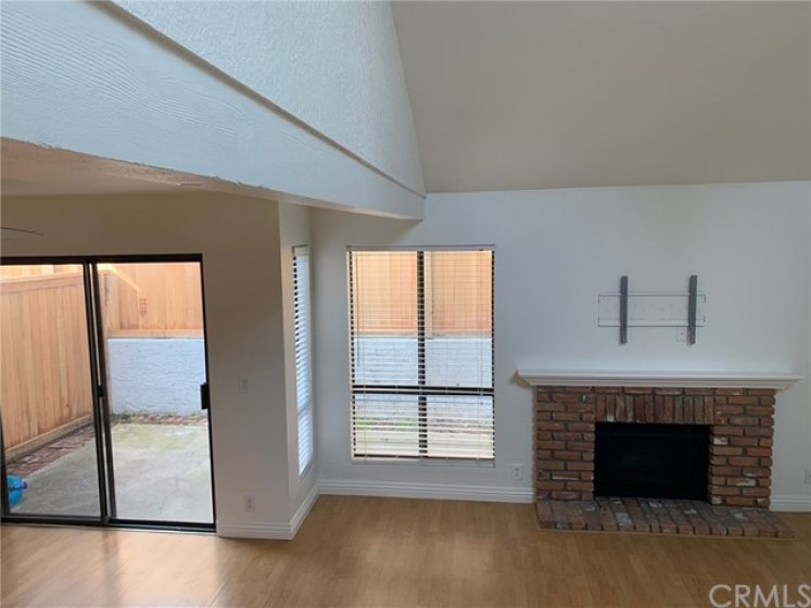 Living room fireplace with views of outdoor patio