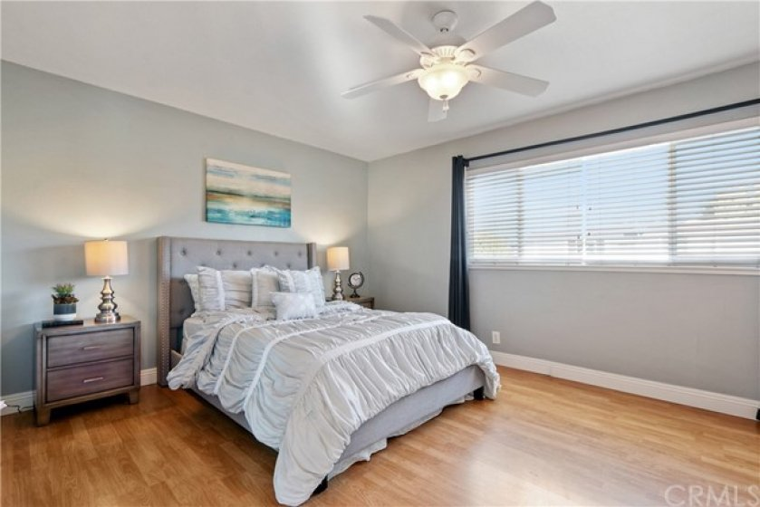 The master bedroom features hardwood flooring, plenty of windows and a ceiling fan with light!