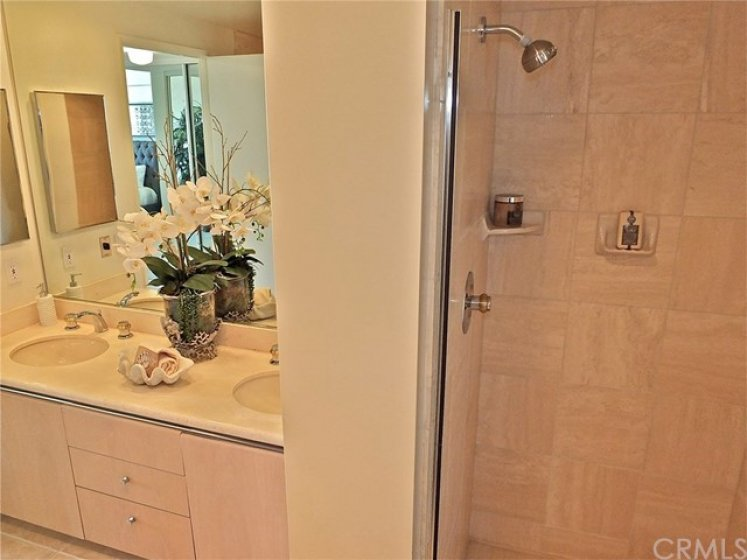 Mater bathroom includes double vanity sink with large mirror above and medicine cabinet in wall.  Plus there is a separate tiled stall shower.