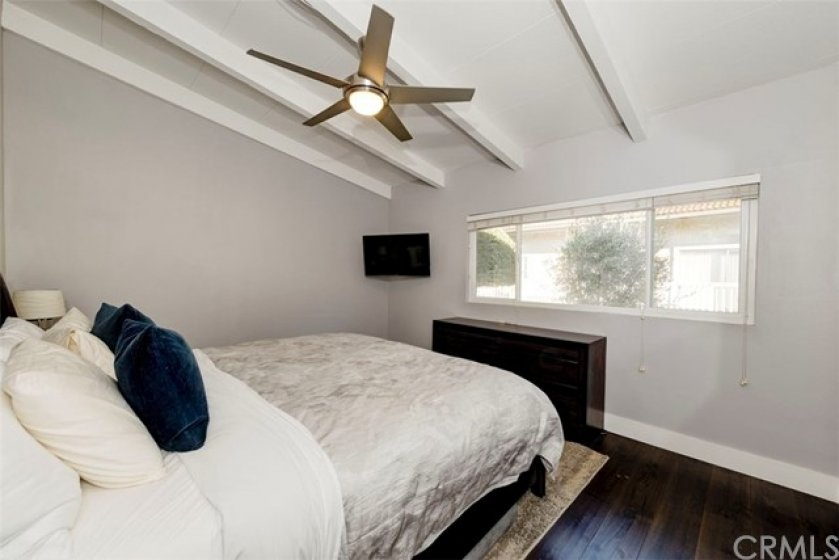 Secondary Bedroom with ceiling fan, hardwood floors and custom closet.