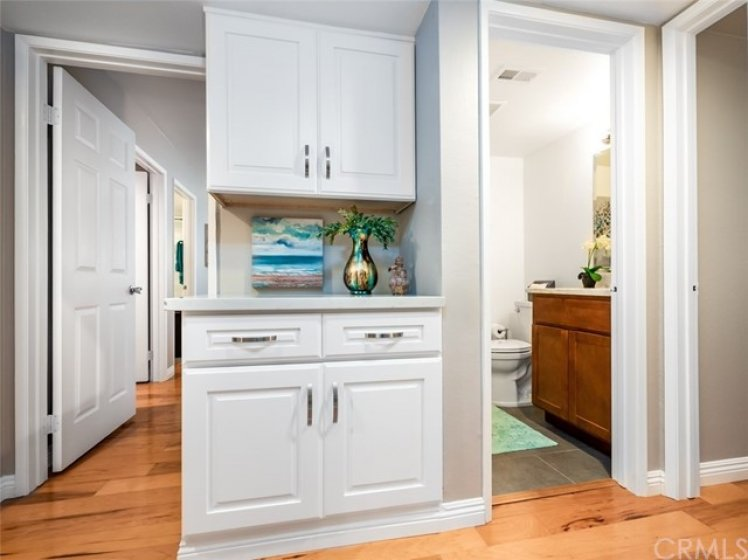 now in Hall with wood floors and stunning linen cabinets with quartz counter