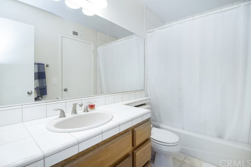 Full 2nd floor guest bath with tile counters, flooring & tub surround.  Easy access from hallway and master bedroom.