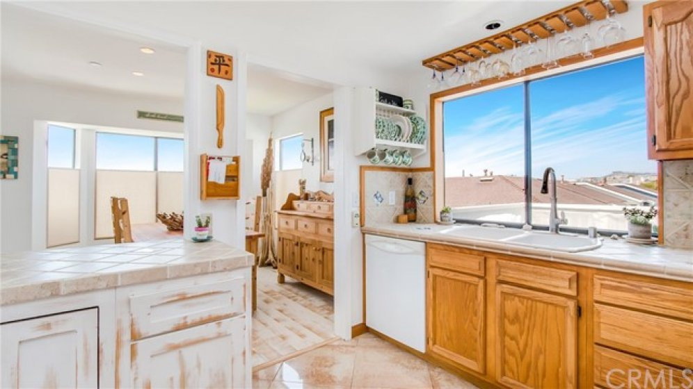 Kitchen with large window, double sink, ocean views.