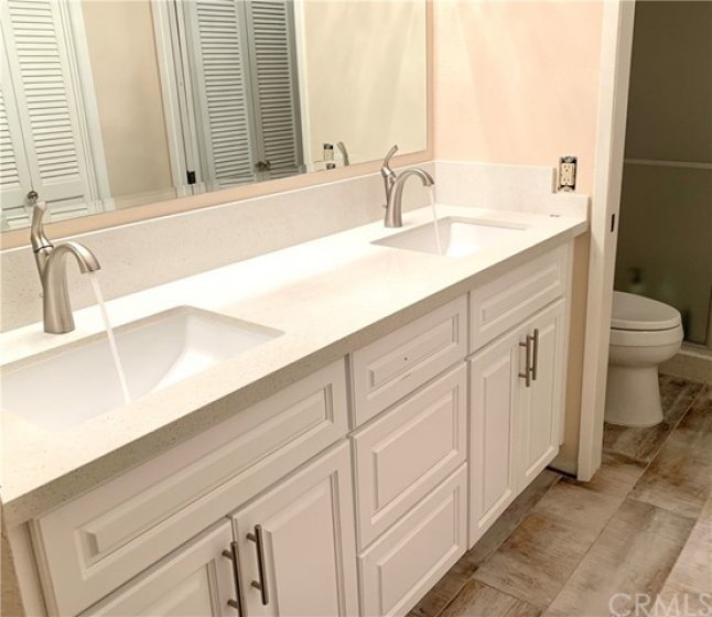 New bathroom quartz counter top with cabinets and faucets.