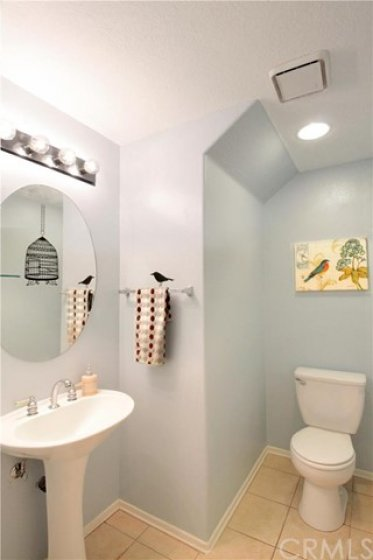 Spacious powder room with pedestal sink & oval mirror downstairs.