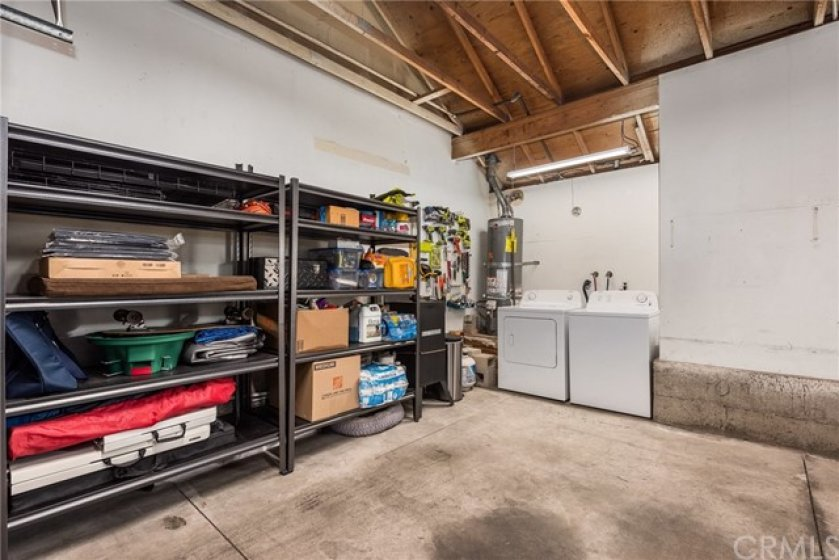 Laundry is in the garage, with additional shelving for storage.
