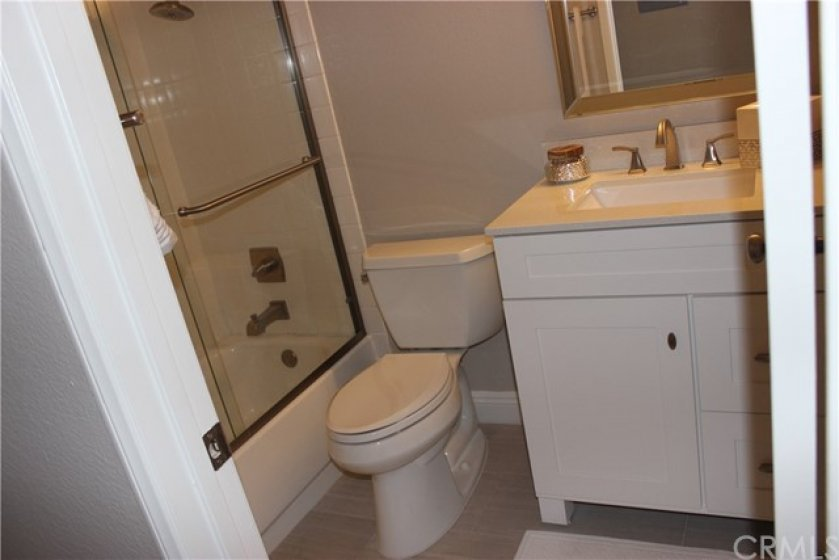 Secondary bathroom with new flooring, toilet and fixtures.