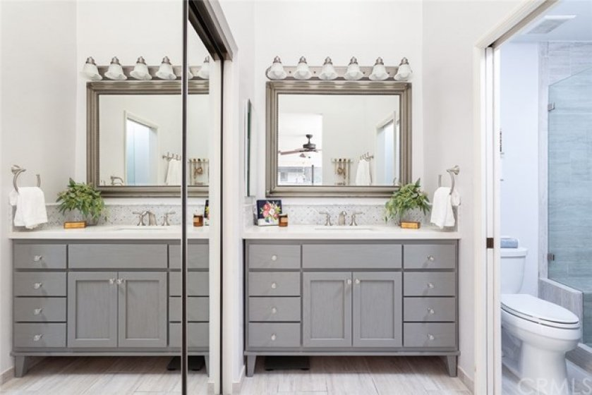 Elegantly remodeled master bath features a large skylight providing great natural light, spacious vanity with plentiful storage, & mirrored closets with custom organizers.