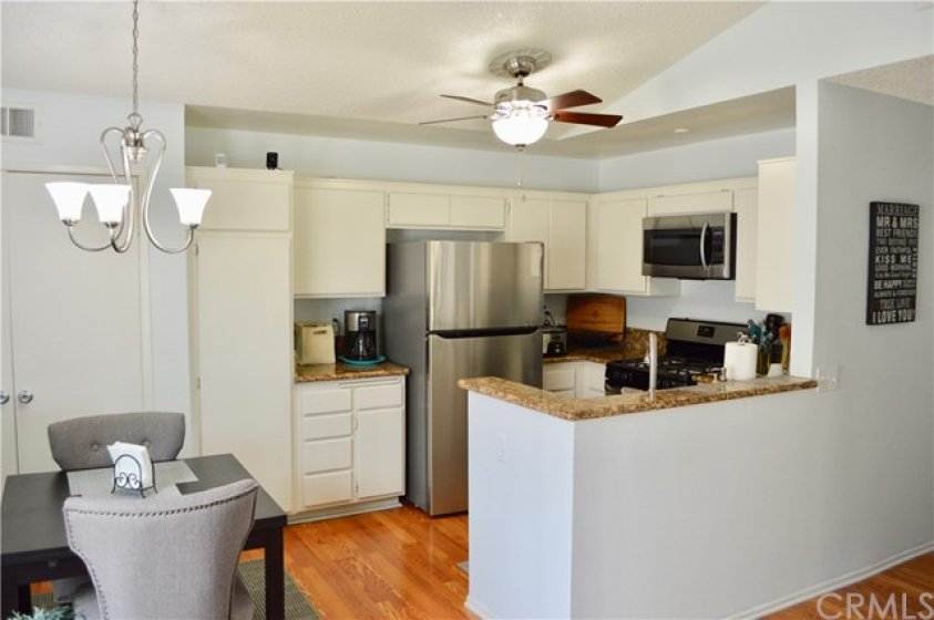 White kitchen with upgraded granite countertops and stainless-steel appliances. Refrigerator is included.