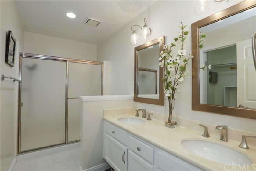 Master bathroom with dual vanity, shower and walk-in closet