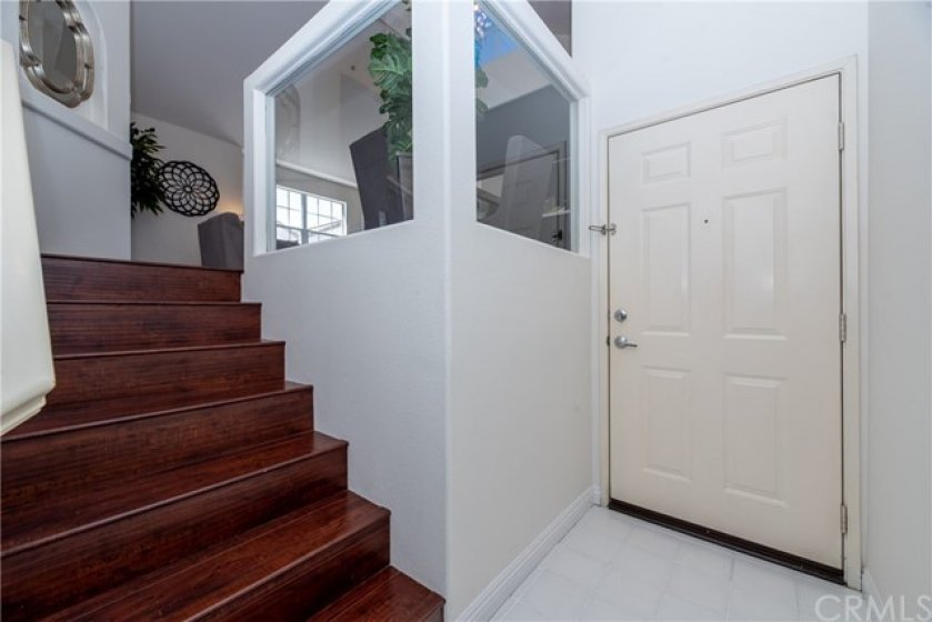 Well laid tiles and laminated wood floors line the entryway