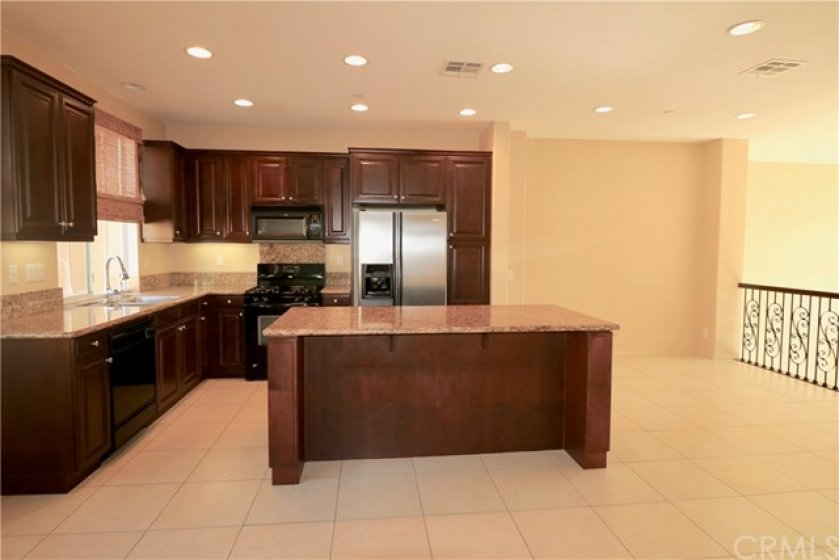 Open Kitchen with Granite Counters and Island and Stainless Refrigerator