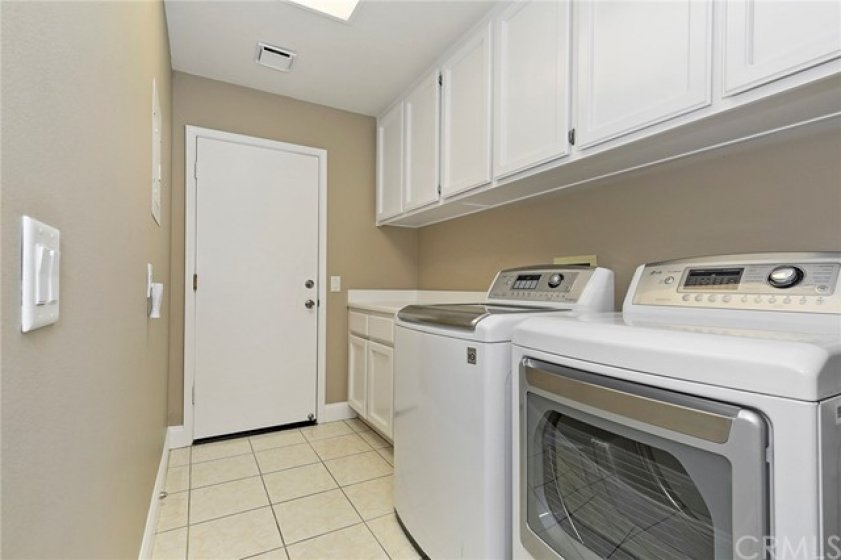 Laundry room with cabinets and direct access to the 2-car garage