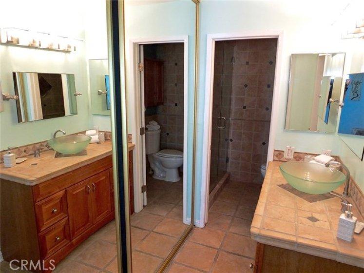 Large mirror closet doors in the bathroom vanity area.