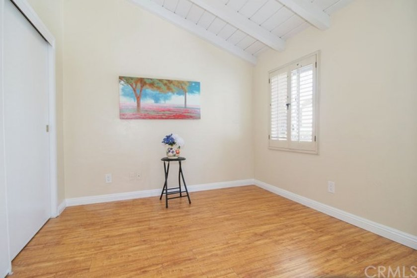 This spacious second bedroom with a window, base molding, wood laminate flooring,  and large closet.