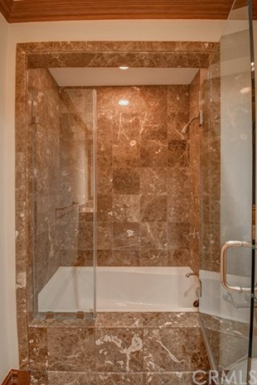 Guest bath with glass enclosed tub and shower