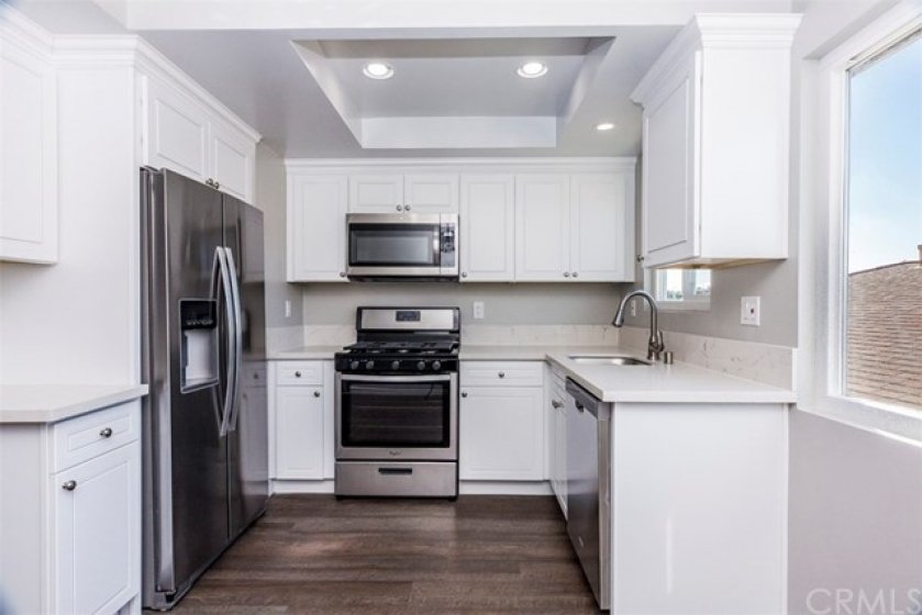 Designer kitchen with recessed lighting, brand new self closing cabinets, Quartz counter tops and Whirlpool Stainless Steel Appliances.